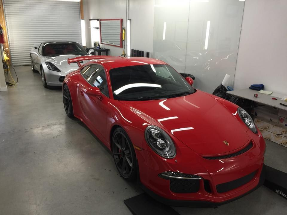 | Porsche and Corvette in the garage waiting for XPEL ULTIMATE installations